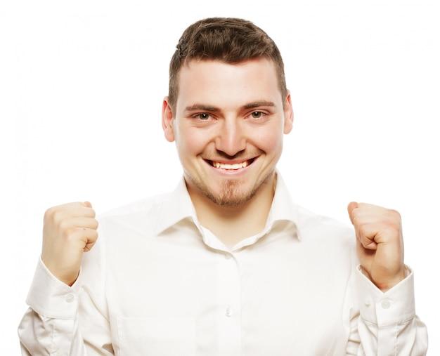 Образ жизни, бизнес и люди концепция: успешный бизнесмен. счастливый молодой человек в строгой одежде жестикулирует и улыбается, стоя на белом фоне