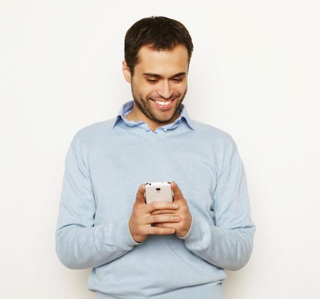 라이프 스타일, 비즈니스 및 사람 개념: 휴대 전화를 사용하는 젊은 사업가. 흰색 배경 위에.