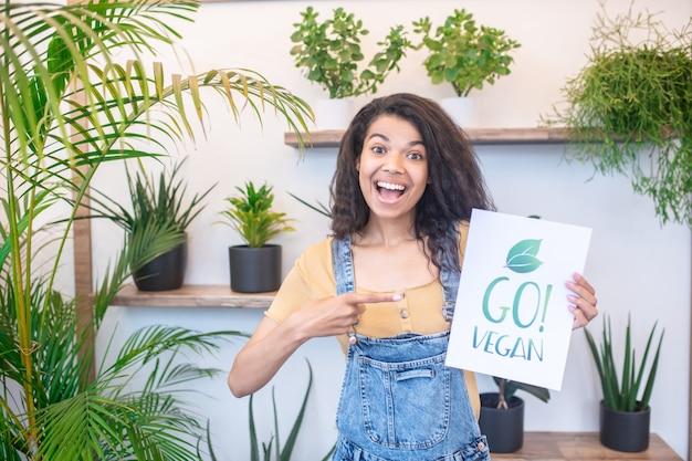 Стиль жизни. веселая красивая женщина с открытым ртом, указывая пальцем на веганский плакат в комнате с зелеными растениями