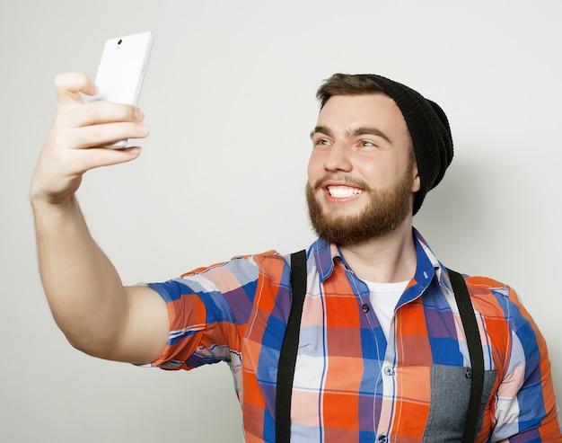 Концепция образа жизни: молодой человек с бородой в рубашке держит мобильный телефон и фотографирует себя, стоя на сером фоне.