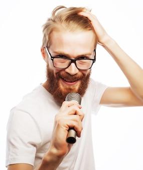라이프 스타일 개념:마이크를 들고 노래를 부르고 흰색 셔츠를 입고 수염을 가진 젊은 남자. 흰색에 격리.