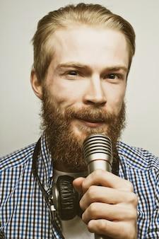 라이프 스타일 개념:마이크를 들고 노래하는 흰색 셔츠를 입고 수염을 기른 젊은 남자. 회색 배경 위에.