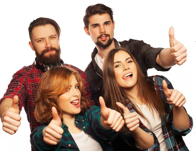 라이프 스타일, 교육 및 사람 개념: 엄지손가락을 보여주는 학생들의 행복한 팀. 스튜디오 흰색 배경 위에 쐈 어. 힙스터 스타일. 특별한 토닝.
