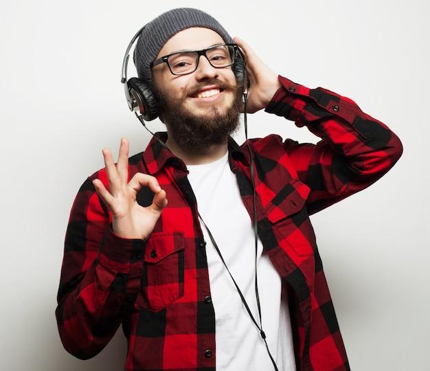 Образ жизни, образование и люди концепции: молодой бородатый человек, слушающий музыку, стоя на сером фоне. хипстерский стиль.