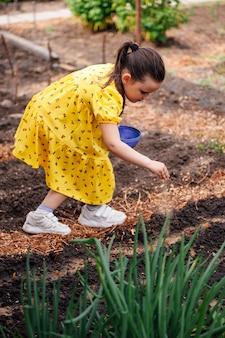 드레스를 입은 초등학생 소녀의 라이프 스타일 전신 초상화는 정원에서 그녀의 부모를 돕습니다 ...