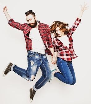 Концепция образа жизни, счастья и людей: счастливая влюбленная пара. прыжки через светло-серый фон. специальная модная тонировка.