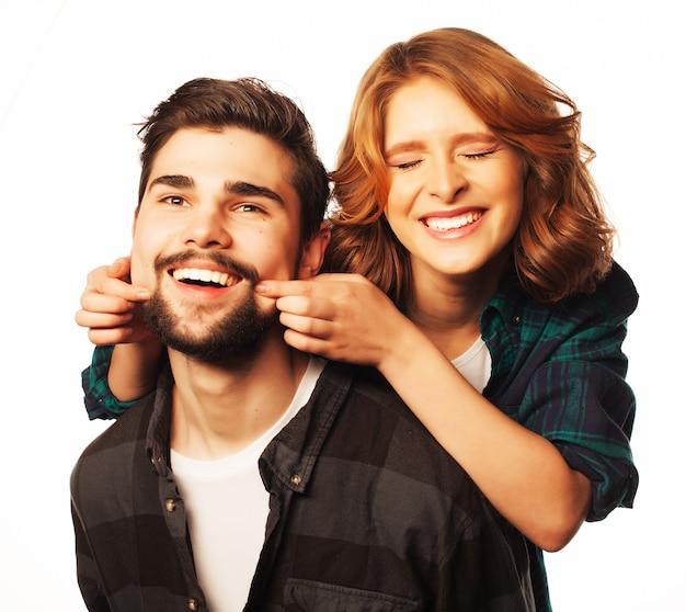 Концепция образа жизни, счастья и людей: счастливая влюбленная пара. молодой человек совмещает свою подругу. студия выстрелил на белом фоне. специальные модные тонирующие фотографии.