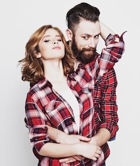 ライフスタイル、幸福、人々の概念:流行に敏感なカップル。ホワイトスペースに対して立っている間ポーズ美しい若い夫婦。