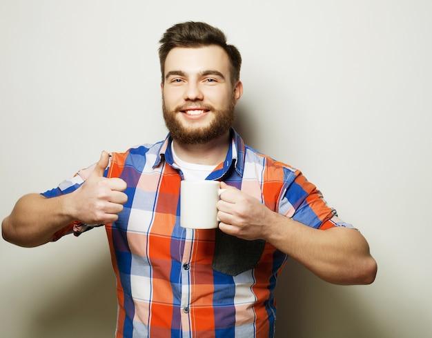 Концепция образа жизни, счастья и людей: молодой бородатый мужчина с чашкой кофе в руке и показывает хорошо, на сером фоне.