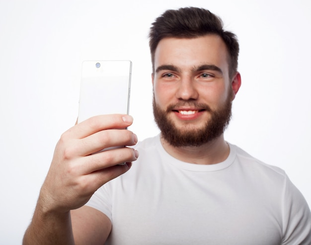 ライフスタイル、幸福、人々の概念:灰色の空間に対して手に携帯電話を持つ若者を生やした。