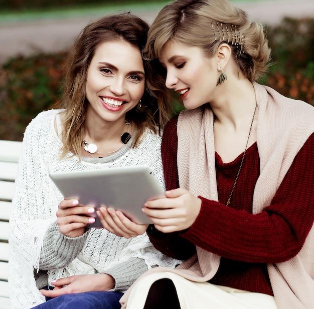 ライフ スタイル、幸福、感情、人々 の概念: タブレットを屋外で使用する美しい女性の女の子の秋