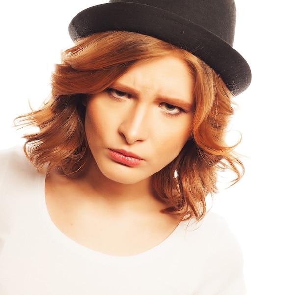 Концепция образа жизни, счастья, эмоций и людей: красивая молодая женщина в белой рубашке и черной шляпе смотрит в камеру и вызывает разные эмоции, стоя на белом фоне