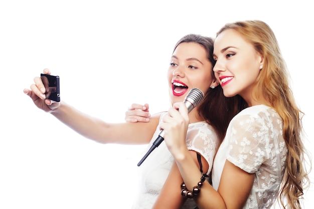 Стиль жизни, счастье, эмоциональная и люди концепция: девушки красоты с микрофоном поют и делают селфи