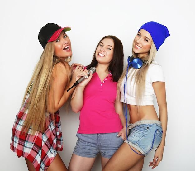 Стиль жизни, счастье, эмоциональная и люди концепция: хипстерские девушки красоты с микрофоном поют и веселятся