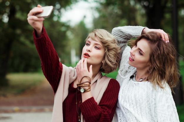 ライフスタイル、幸福、感情的な人々の概念:selfieを作る友達。秋の公園でselfieを作る2つの美しい若い女性。