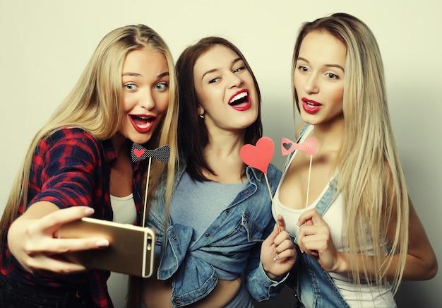Стиль жизни, счастье, эмоциональная и люди концепция: веселые девушки, готовые к вечеринке, селфи