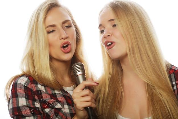 ライフスタイル、幸福、感情、人々のコンセプト: マイクを持った2人の美女が歌い、楽しむ