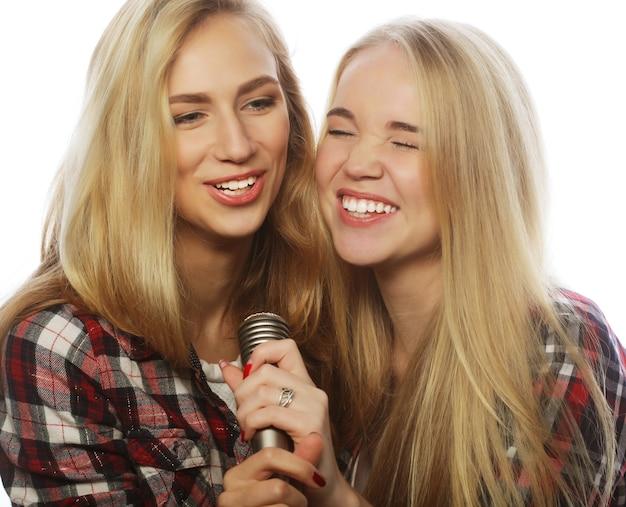 라이프 스타일, 행복, 정서 및 사람 개념 : 마이크 노래와 재미를 가진 두 명의 아름다움 소녀