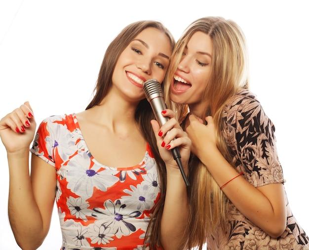 Стиль жизни, счастье, эмоциональная и люди концепция: две девушки красоты с микрофоном поют и веселятся