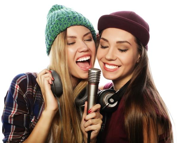 Стиль жизни, счастье, эмоции и люди концепции: две девушки-хипстеры красоты с микрофоном поют и веселятся