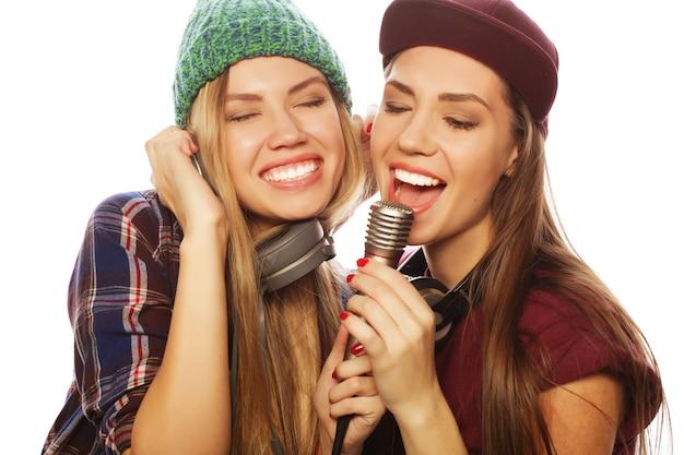 Стиль жизни, счастье, эмоциональная и люди концепция: две девушки-хипстеры красоты с микрофоном поют и веселятся