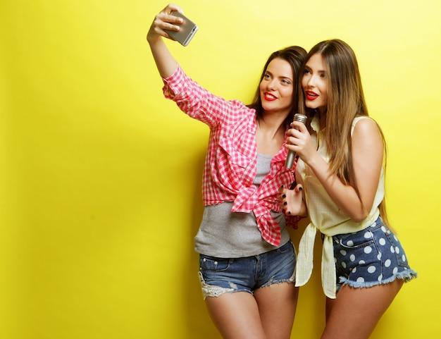 라이프 스타일, 행복, 정서 및 사람들 개념 : 마이크가있는 두 명의 뷰티 힙 스터 소녀가 노란색 배경 위에 셀카를 가져갑니다.