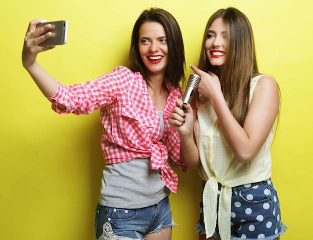 라이프 스타일, 행복, 정서 및 사람 개념 : 마이크가있는 두 명의 뷰티 힙 스터 소녀가 노란색 배경 위에 셀카를 가져갑니다.