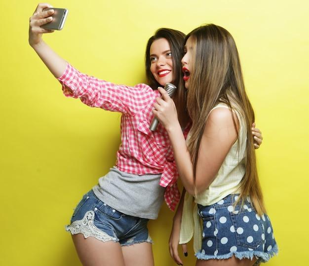 Концепция образа жизни, счастья, эмоций и людей: две девушки-хипстеры красоты с микрофоном делают селфи на желтом фоне
