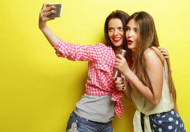 Концепция стиля жизни, счастья, эмоций и людей: две девушки-хипстеры красоты с микрофоном делают селфи на желтом фоне