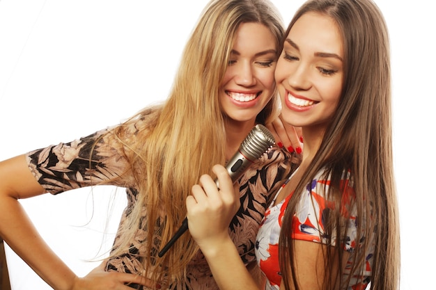 ライフスタイル、幸福、感情と人々の概念:白い背景の上で歌う2人の若い女の子