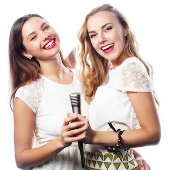 Концепция образа жизни, счастья, эмоциональной и людей: две молодые девушки поют, на белом фоне