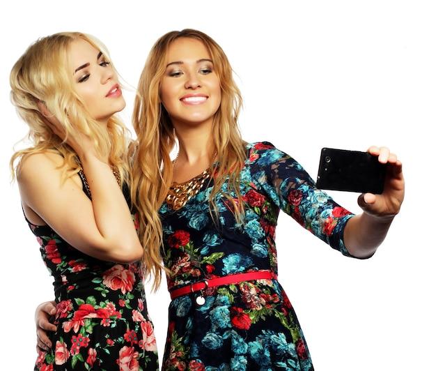 ライフ スタイル、幸福、感情、人々 の概念: 携帯電話で自撮りを取る 2 人の若い女性