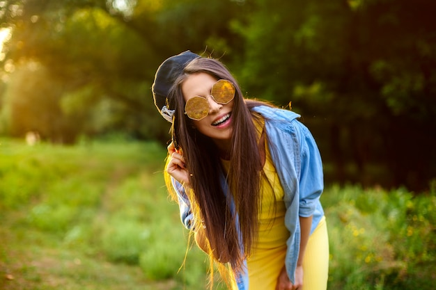 Life style. happy girl in sunglasses and a cap in bright clothes in a park at sunset