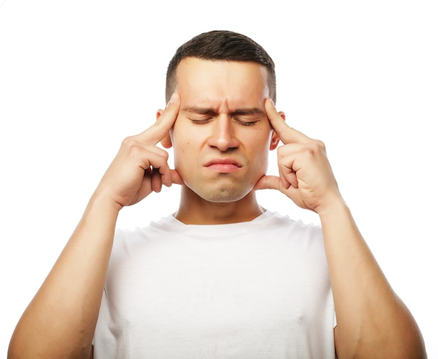 Life style and people concept: attractive young man suffering of strong headache