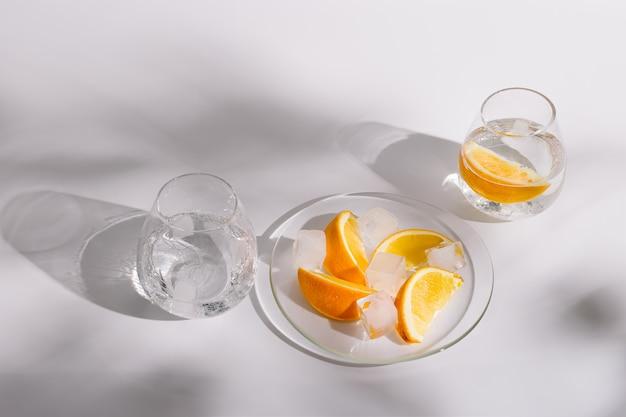 신선한 냉수와 오렌지 조각이 담긴 유리 컵이있는 라이프 스타일 사진