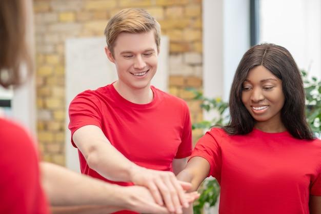 생활 양식. 초점을 맞춘 젊은 백인 남자와 자선 단체에서 화합의 손 기호로 보여주는 어두운 피부 소녀 미소