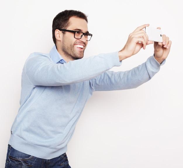 Концепция образа жизни, технологий и людей: молодой человек в рубашке держит мобильный телефон и фотографирует себя, стоя на белом фоне.