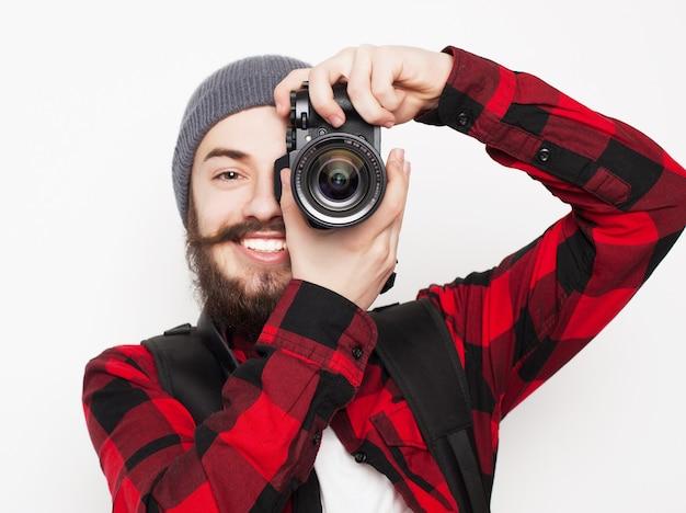 라이프 스타일, 기술 및 사람 개념: 전문 사진 작가. 흰색 배경 위에 카메라를 들고 셔츠에 자신감이 젊은 남자의 초상화