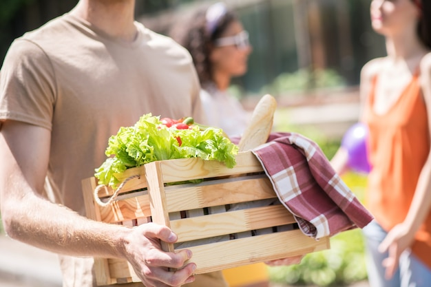 Life style. wooden box with fresh vegetables and delicious bread in hands of guy for picnic and girlfriend behind outdoors