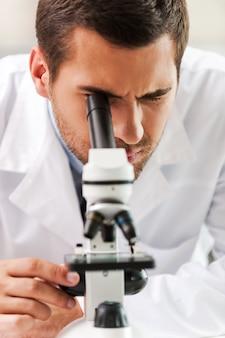 현미경 아래의 삶. 실험실에서 일하는 동안 현미경을 사용하여 흰색 제복을 입은 집중된 젊은 과학자