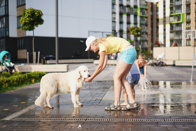 Life with domestic pets in the city, young woman watering a dog with water from a fountain