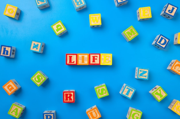 Life, wooden surface colorful alphabet blocks on blue, flat lay, top view