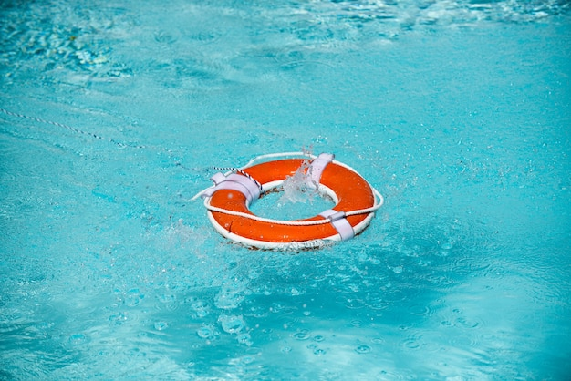 Lifebelt on sea or pool orange inflatable ring floating in blue water life buoy for protect and safe...