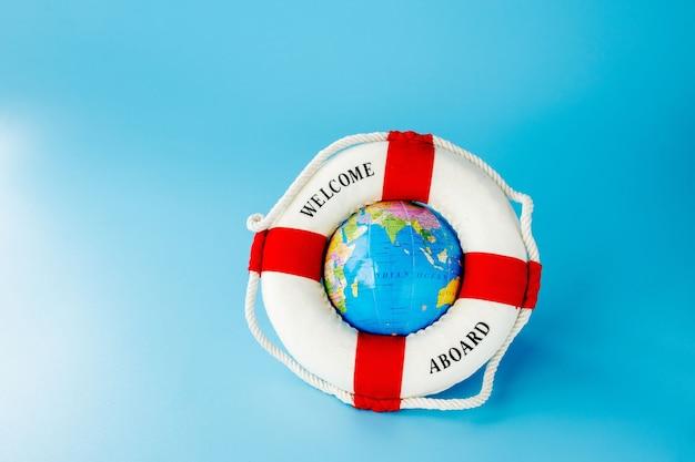 Lifebuoy 및 파란색 배경에 글로브입니다. 여름 또는 휴가 개념. 공간을 복사하십시오.