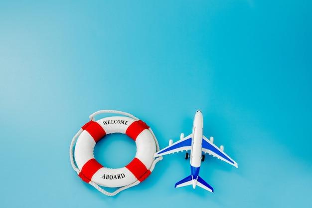 Спасательный круг и модель самолета на синем фоне. концепция лета или отпуска. скопируйте пространство.
