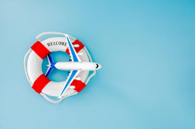 Lifebuoy 및 파란색 배경에 비행기의 모델. 여름 또는 휴가 개념. 공간을 복사하십시오.