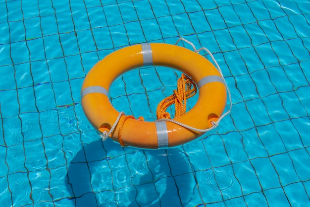 Lifebuoy floating on top of sunny blue water in swimming pool