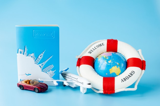Lifebuoy, globe, model of airplane and car on blue surface