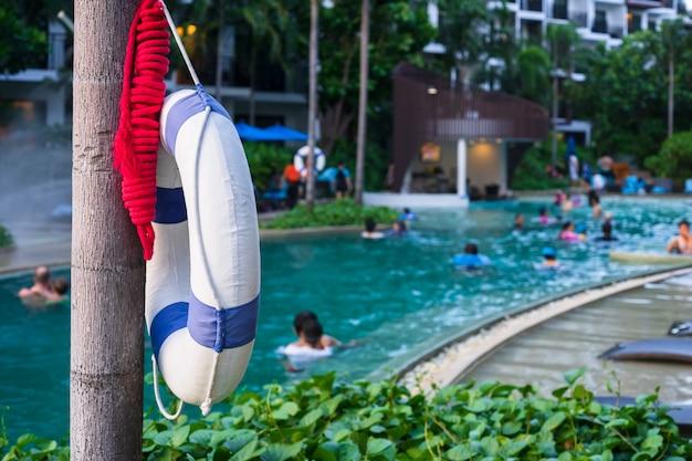 Спасательный круг висит на дереве рядом с открытым бассейном