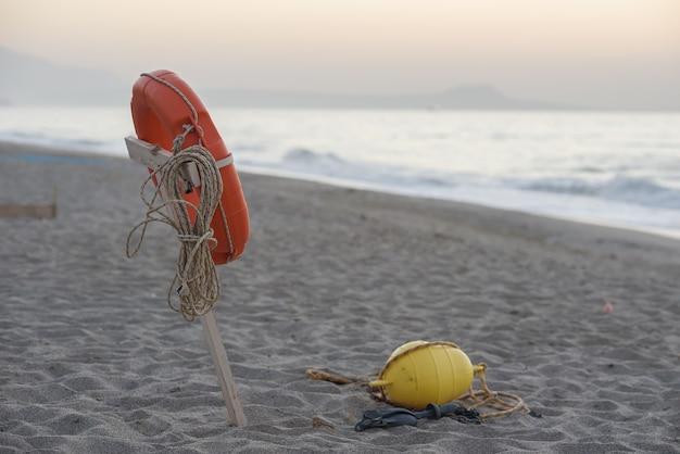Спасательный круг висит на деревянном шесте на пляже и на фоне моря на закате, спасая концепцию жизни